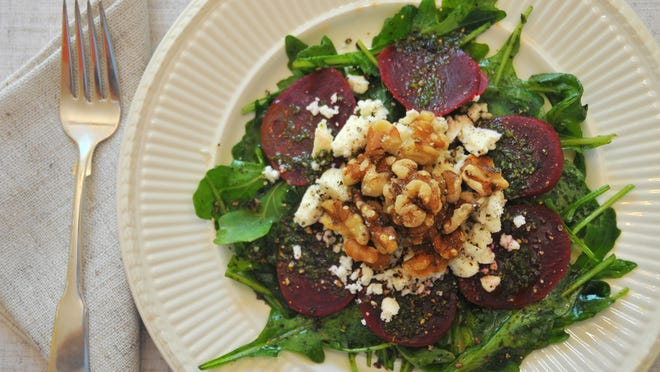 Arugula, beets, goat cheese and walnuts mingle well together for a light summer salad.