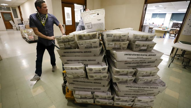 Chet Harhut, deputy manager, of the Allegheny County Division of Elections, wheels a dolly loaded with mail-in ballots, at the division of elections offices in downtown Pittsburgh Wednesday, May 27, 2020. The once-delayed Jun 2 Pennsylvania primary will feature legislative and congressional races, a first run for some new paper-record voting systems and the inaugural use of newly legalized mail-in ballots. (AP Photo/Gene J. Puskar)