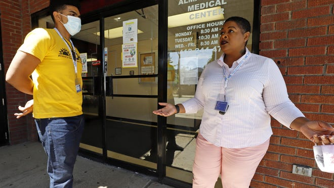 Kiva A. Fisher-Green, right, talks with fellow social worker Tyree R. Ford on Monday outside the Alma Illery Medical Center in Pittsburgh. In March and April, when Philadelphia and its surroundings became one of the nation's hot-spots for COVID-19 cases, Pittsburgh seemed at the time, to be under more control: the city racked up a fraction of the coronavirus cases as the other side of Pennsylvania. But by the beginning of July, officials in Pittsburgh's Allegheny County, began a cascading shutdown of bars, restaurants and gatherings due to an alarming spike in COVID-19 cases.