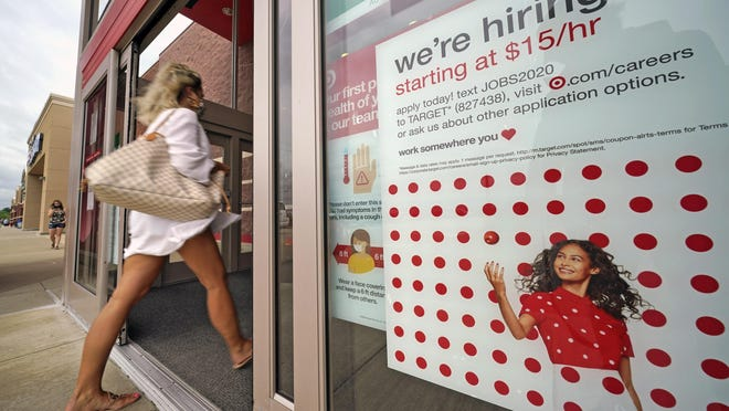 FILE - In this Sept. 2, 2020, file photo, a help wanted sign hangs on the door of a Target store in Uniontown, Pa. The government issues the jobs report Friday, Sept. 4, for August at a time of continuing layoffs and high unemployment.
