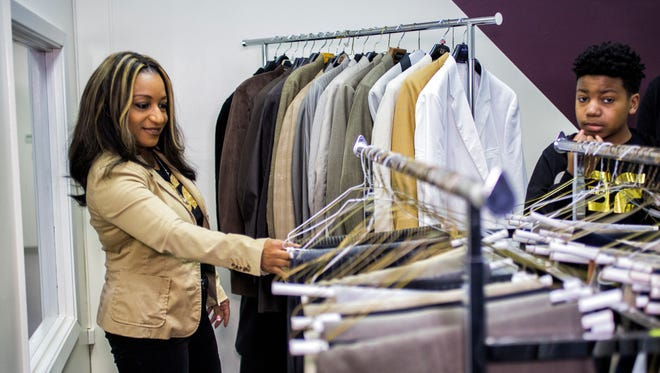 "Towanda Peete-Smith and her son, Braylon Smith, look at men's clothing during the grand opening of the Bernal E. Smith II Empowerment Center on Feb. 28, 2018, at 413 N. Cleveland, inside the Memphis Urban League. Peete-Smith, the wife of the late Tri-State Defender publisher, donated over 150 suits, shirts, ties and shoes to the Memphis Urban League's ""Save Our Sons"" Initiative. Smith was a board member of the Memphis Urban League and supporter of the initiative. The center will provide suits, counseling and other help for struggling African-American men."