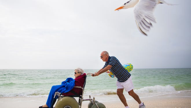 Russ Thomas pushes his friend Solveig Birkeland down the beach, chasing seagulls, on Friday, January 12, 2018 on Barefoot Beach in Bonita Springs. Birkeland celebrated her 102nd birthday with her daughter and friends on the beach.