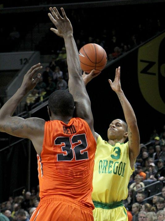 Oregon's Joseph Young, right, shoots a 3-pointer over Oregon State's Jarmal Reid during the second half of an NCAA college basketball game in Eugene, Ore., Saturday, Jan. 3, 2015. (AP Photo/Chris Pietsch)
