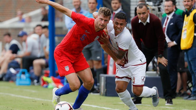 U.S. defender Walker Zimmerman, left, battles Venezuela midfielder Darwin Machis during an international friendly on June 9. 2019. Zimmerman will join Nashville SC for the club's debut season after a trade with LAFC.