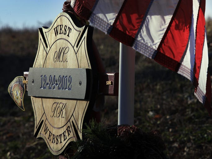 This memorial plaque honors West Webster firefighters Mike Chiapperini and Tomasz Kaczowka along Lake Road, where they were killed on Christmas Eve of 2012.