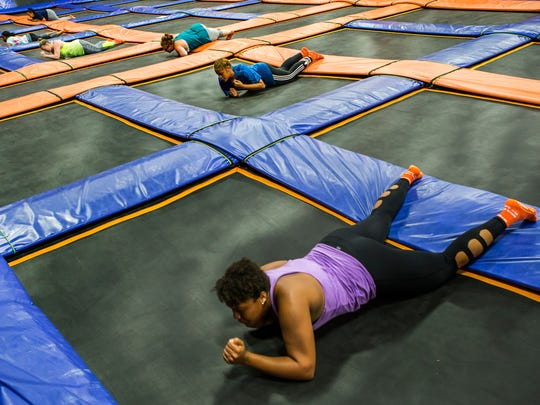 Students in Devon White's trampoline aerobics class crawl across the trampolines at Skyzone in Newark on Wednesday evening.