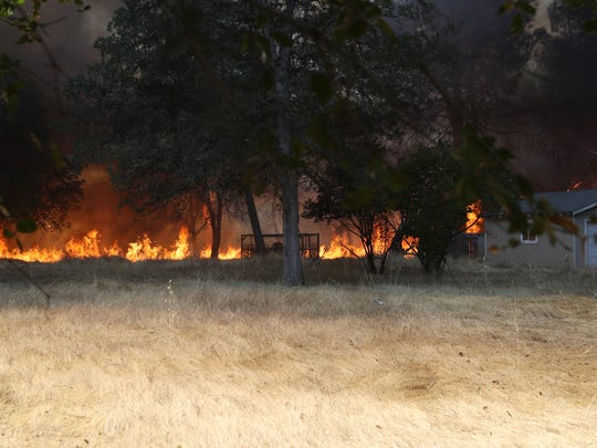 Fire moves across dry grass Tuesday in Happy Valley.
