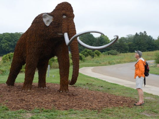 Brian Clark examines a wooly mammoth sculpture at the