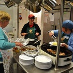 Volunteers prepare a holiday meal, coordinated by the Interfaith Council of Churches in Gettysburg, for homeless people. Pictured from left to right are Annie Springer, Deb Wood and Helen Cook.
