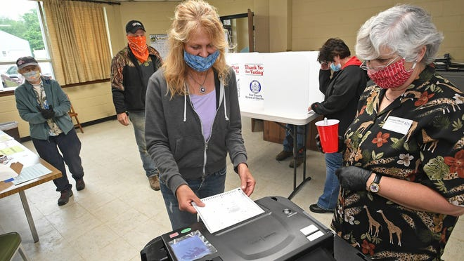 Sherri Porter feeds her ballot into a scanner after voting in the primary Tuesday at the LeBoeuf Township Municipal Building, 14270 Flatts Road. At right is ballot scanner inspector Ginger Bollinger.