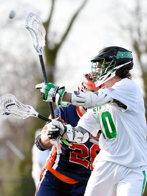York College's Cameron Leech passes the ball against Gettysburg's Will DeMartin in the second half of a college men's lacrosse game Wednesday at York College. York College defeated Gettysburg College, 9-7.