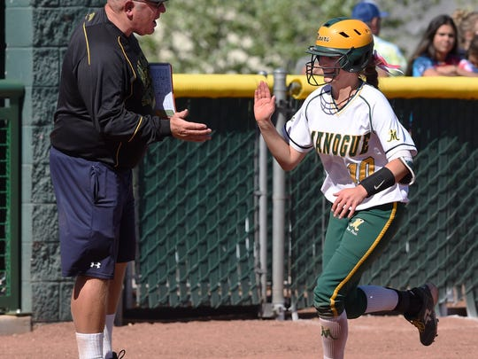Manogue's Magan Lawson gets five from coach after hitting a home run against Douglas in Thursday's playoff game at Bishop Manogue.