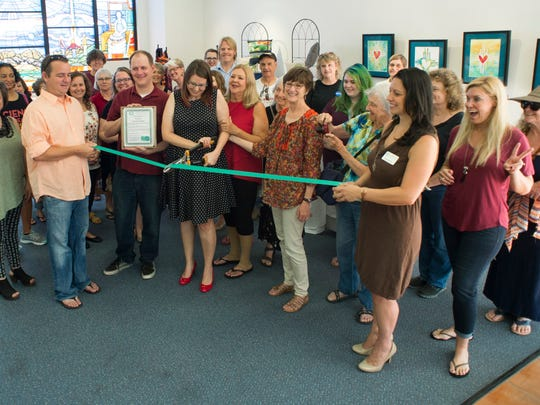 Rachel Courtney cuts the ribbon, officially opening her store, Pretty Nice Creations, in the Tombaugh Gallery of the Unitarian Universalist Church of Las Cruces.