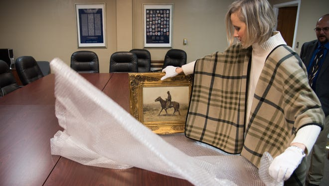 Laura Huckaby, assistant director of the San Angelo Museum of Fine Arts, carefully wraps a painting that had been reported stolen from City Hall and recovered by the San Angelo Police Department.
