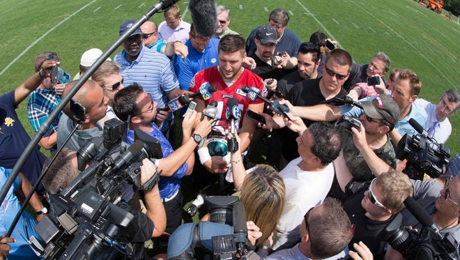 Reporters gather around Tim Tebow during organized team activities on May 28.