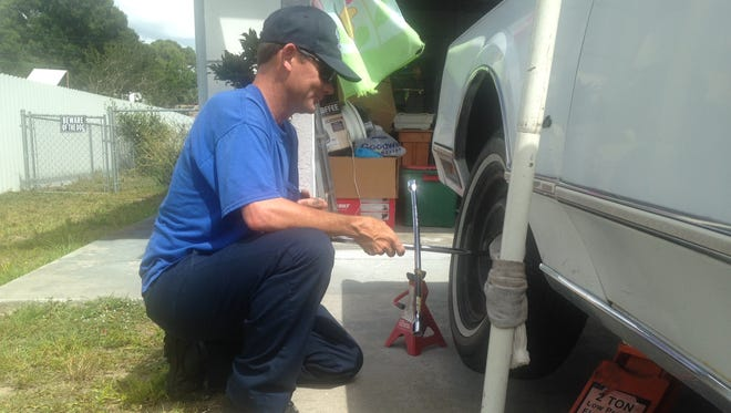Kevin Wood replaces two of the tires slashed on his mother's 1989 Lincoln Town Car. Wood said he put used tires back on because his mother was getting rid of the car soon anyway. Her car was among neat two dozen that has their tires slashed over the weekend.