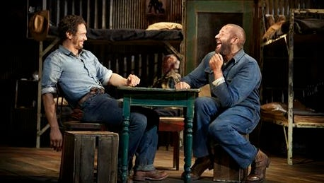 """This image released by Polk & Co. shows James Franco, left, and Chris O'Dowd in a scene from """"Of Mice and Men,"""" in New York.  A high-definition broadcast of Franco starring on Broadway this summer in John Steinbeck's """"Of Mice and Men"""" will compete with the movies """"Nightcrawler"""" and """"Gone Girl"""" at the box office, and it marks an important milestone. While a few Broadway shows have been broadcast, this is the first time the National Theatre Live series, the gold standard, has chosen a Broadway show to beam into over 900 venues across the U.S. and Canada."""