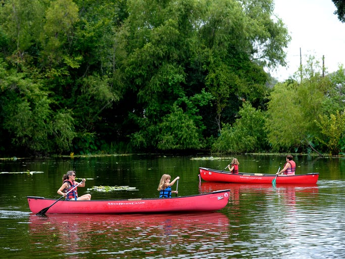 Visitors paddle canoes in a pond during Acadian Culture Day at Vermilionville in Lafayette, La., Sunday, Aug. 3, 2014. Paul Kieu, The Advertiser