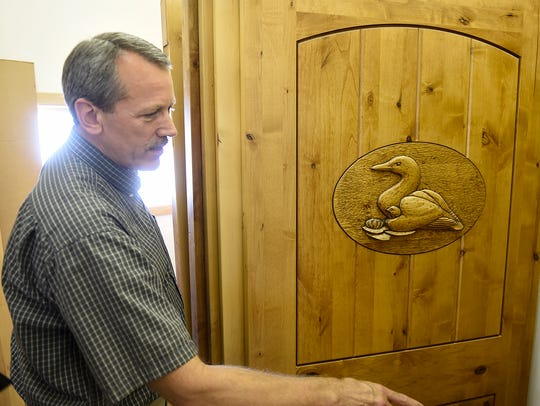 Owner Tim Worms shows examples of custom hand-carving