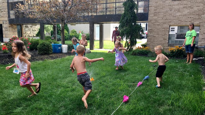 Children enjoy playing tug-of-war and running through a sprinkler at Vacation Bible School at St. John's Church in Fremont.