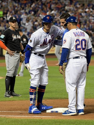 New York Mets' Brandon Nimmo (9) talks with first base coach Ruben Amaro Jr. (20) and a trainer after getting injured running out a single during the seventh inning of a baseball game as Miami Marlins first baseman Peter O'Brien, left, looks on Saturday, Sept. 29, 2018, in New York. (AP Photo/Bill Kostroun)