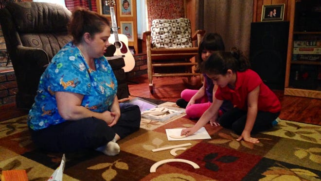 Abby Pace (right), 5, places wooden pieces over a large capital S to create the letter in the proper order. The action is one step of an activity that teaches letter recognition and helps young children create a motor plan for drawing letters. Pediatric occupational therapist Stephanie Riley (left) facilitates the activity with Abby and her sister Emma (center) at Riley's home.