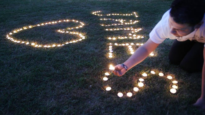 Votive candles are lighted during a vigil for James Foley in his hometown of Rochester, N.H., on Aug. 23, 2014. Foley, a freelance journalist, was murdered earlier in the week by ISIS militants
