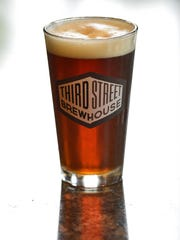 A glass of Spotlight Rye IPA gleams in the light Wednesday at Third Street Brewhouse in Cold Spring.