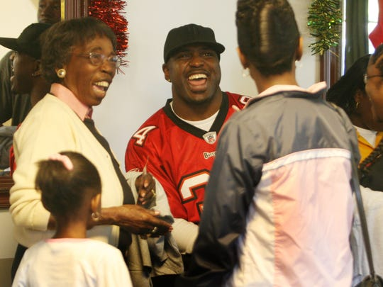 "2008: Earnest Graham, of the Tampa Bay Bucs, visits with Veronica Shoemaker, left, and other visitors to the Source of Light and Hope House on Tuesday, December 23, 2008. Foster children at the Hope House were given gifts courtesy of ""Earnest Giving"" which is Earnest Graham's Charitable Organization. Members of SunTrust Bank made a charitable donation of 5,000 dollars that was presented to Graham during his visit."