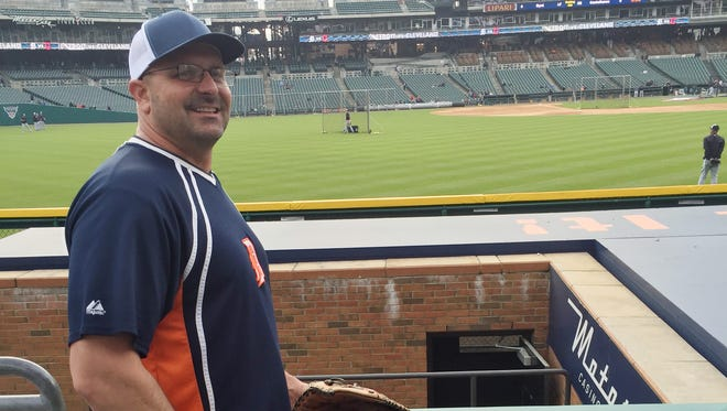 Bill Dugan, 39, of Roseville takes a break while awaiting home run balls in the left field stands of Comerica Park in Detroit on Friday, April 22, 2016.
