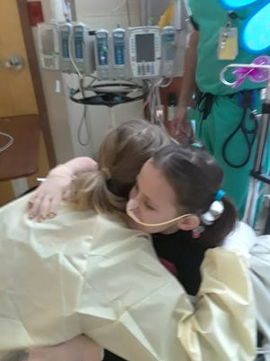 Taylor Swift hugs 8-year-old Isabella McCune on May 5, 2018. Isabella was badly burned in an accident and had made a video hoping Swift would come visit her in the Arizona Burn Center.