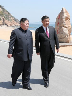 Chinese President Xi Jinping, right, walks with North Korean leader Kim Jong Un during a meeting in Dalian in northeastern China's Liaoning Province this week.