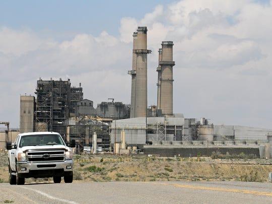A car drives away from the San Juan Generating Station