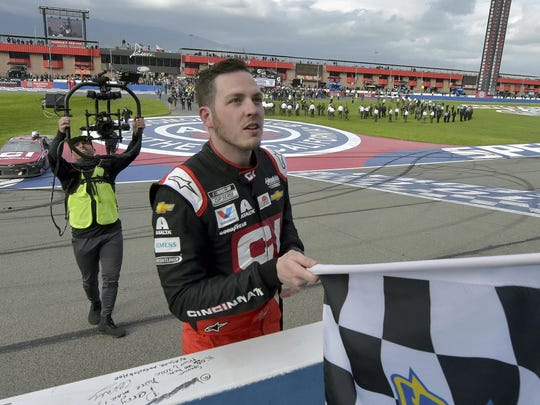 Alex Bowman accepts the checkered flag from an official after winning a NASCAR Cup Series auto race March 1 in Fontana, Calif.