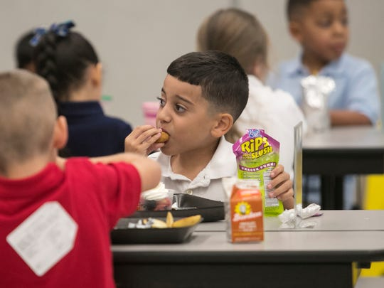 Jonathan Batista, 6, eats lunch with his classmates
