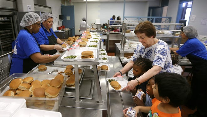 Monica Smith helps her prekindergarten students get lunch at the Montessori School, which shares space in the Freddie Thomas campus with School 16.