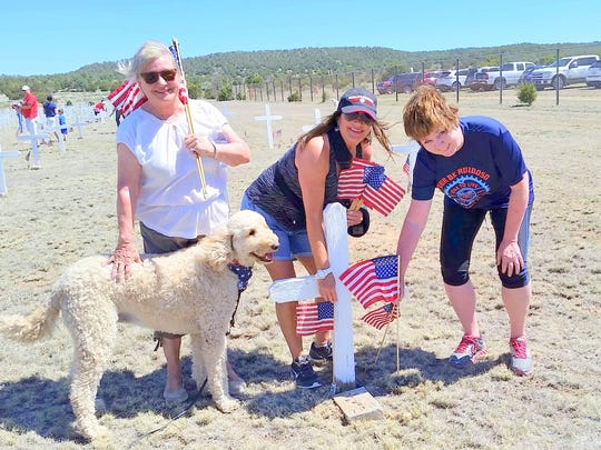 Three volunteers stake their flags while a four-legged