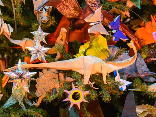 Dinosaurs decorate the origami Christmas tree at the