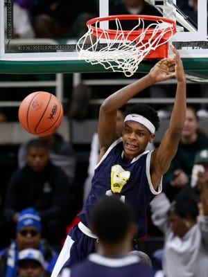 Saginaw Arthur Hill's De'quevion Johnson finishes a dunk off a lob pass in the second half of their 73-61 win over Lansing Everett in the MHSAA boys Class A semifinal basketball game on Friday, March 27, 2015 in East Lansing.