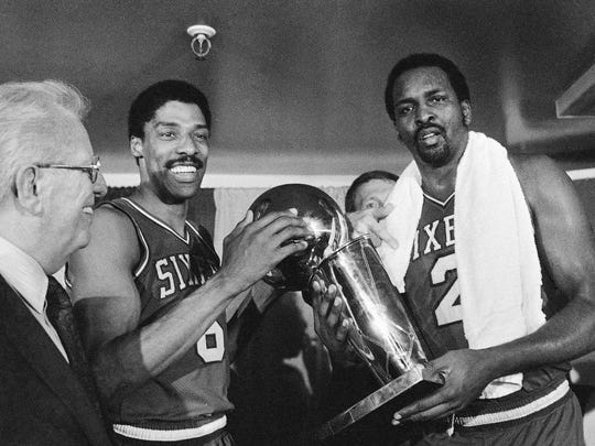 FILE - Julius Erving, left, and Moses Malone, right, hold the NBA Championship trophy Tuesday night May 31, 1983 after defeating the Los Angeles Lakers in four straight games.