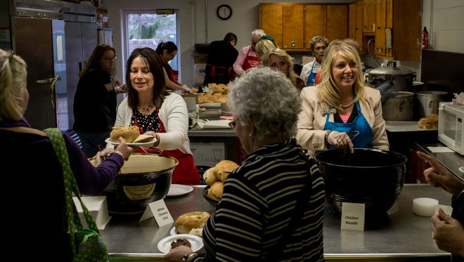 Volunteers Tiffany MacReady, of Port Huron, and Rhonda Bessette, of Fort Gratiot, hand out soup and bread bowls during the annual Empty Bowls fundraiser Thursday, April 21, 2016 at St. Stephen Catholic Church in Port Huron.
