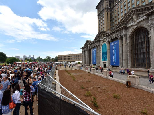 Throngs of people stand in line waiting to tour the Michigan Central Depot in Corktown, Saturday afternoon, June 23, 2018.