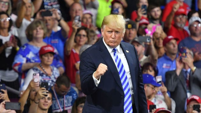 President Donald Trump salutes his supporters after speaking at a political rally at Charleston Civic Center in Charleston, West Virginia on August 21.