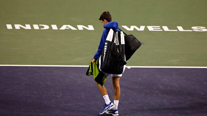 FILE - In this Monday, March 11, 2019, file photo, Novak Djokovic, of Serbia, walks off the court during a rain break in his match against Philipp Kohlschreiber, of Germany, at the BNP Paribas Open tennis tournament in Indian Wells, Calif. The BNP Paribas Open tennis tournament, set to begin Wednesday, March 11, 2020, has been postponed after a case of coronavirus was confirmed in the Coachella Valley.
