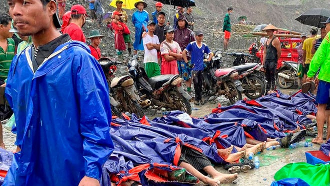 People gather near the bodies of victims of a landslide near a jade mining area in Hpakant, Kachine state, northern Myanmar Thursday, July 2, 2020. Myanmar government says a landslide at a jade mine has killed dozens of people.