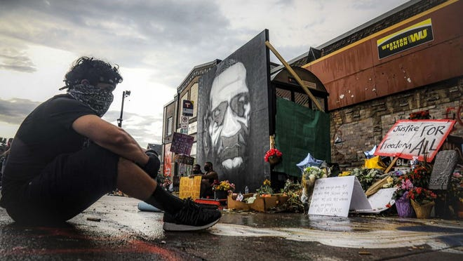 "After a new mural, center, of George Floyd is added to a growing memorial of tributes, Trevor Rodriquez sits alone at the spot where Floyd died while in police custody, Tuesday June 2, 2020, in Minneapolis, Minn. ""I have been out every single night protesting peacefully, just trying to support everything,"" said Rodriquez. ""I didn't want to come here just on a rush, so I had to just take a moment to pay my respect."""