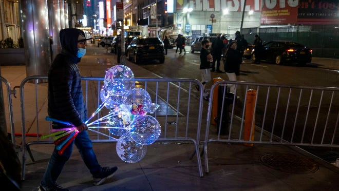 A barricade along Eighth Avenue marks a closed off Times Square in New York, late Thursday, Dec. 31, 2020, as celebrations have been truncated this New Year's Eve due to the ongoing pandemic. Those beyond the barricade were previously approved for entry to the area.