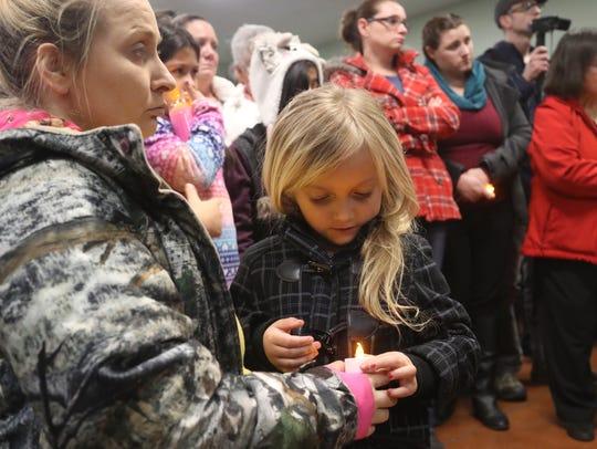Sandra Wells, left, and her daughter Cherokee, 5, listen