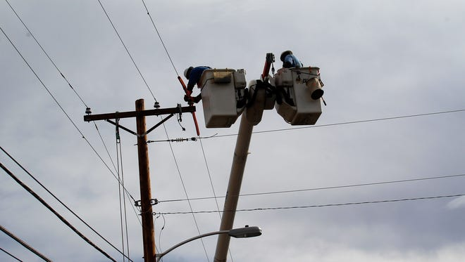 In this file photo, a Farmington Electric Utility System employee works to restore power Friday near Butler Avenue and 18th Street in Farmington after the line was hit by lightning.