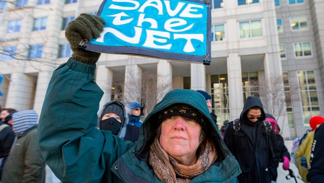 "A woman is pictured holding a ""Save the Net"" protest sign during a demonstration against the proposed repeal of net neutrality outside the Federal Communications Commission headquarters  in Washington, D.C."